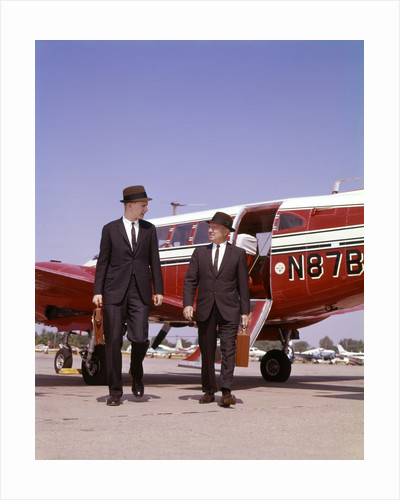 1960s Two Businessmen In Suits And Hats Carrying Briefcases Walking From A Small Twin Prop Business Airplane Talking by Corbis