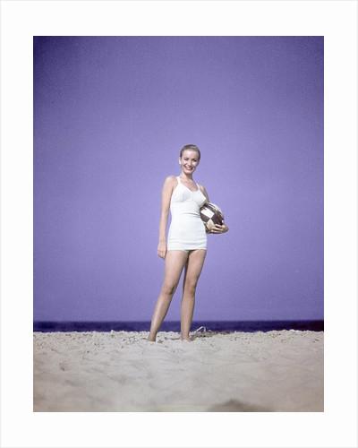 1950s Full Length Portrait Woman Light Blue One Piece Bathing Suit Swim Wear Standing On Sand Holding Beach Ball Fashion by Corbis