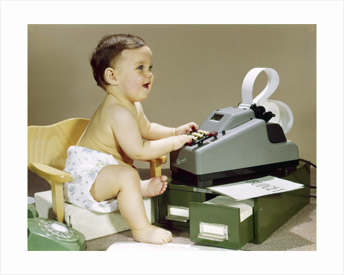 1960s Smiling Accountant Office Worker Baby Wearing Cloth Diaper Sitting In Chair Using Adding Machine Calculator by Corbis