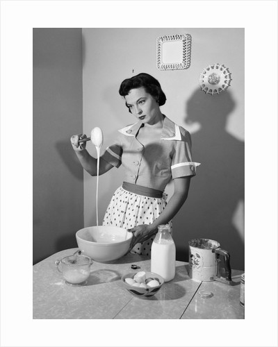 1950s housewife mixing sticky batter in kitchen by Corbis