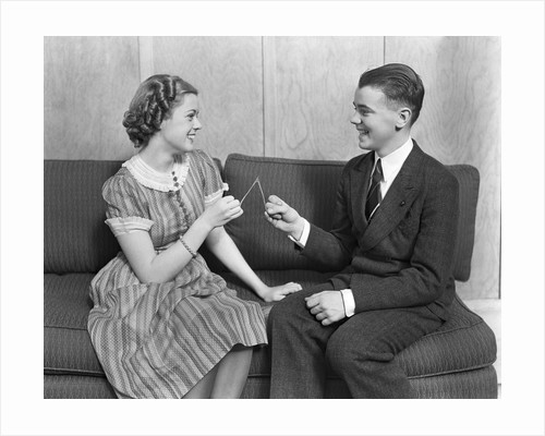 1930s teen boy and girl sitting on a sofa holding wishbone by Corbis