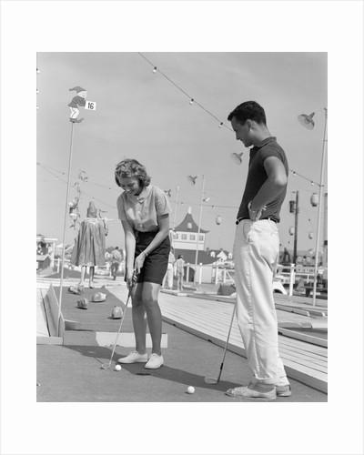 1950s 1960s teenage couple playing miniature golf by Corbis