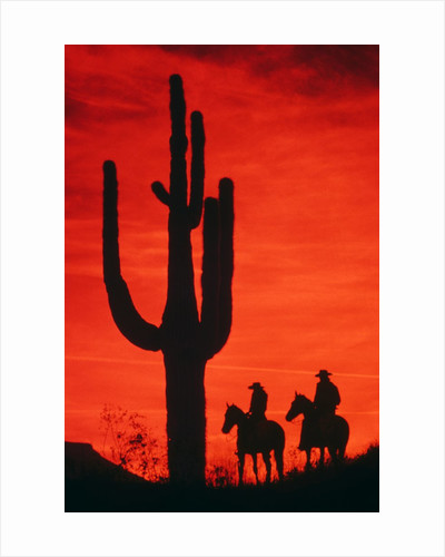 1980s silhouette of two anonymous cowboys riding on horseback by Corbis