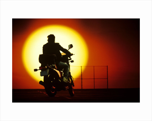 1980s silhouette of anonymous man on motorcycle driving toward rising setting sun by Corbis