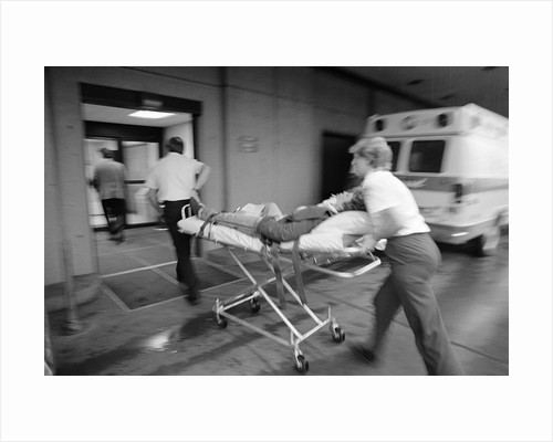 1980s EMT team rushing patient into a hospital on a stretcher by Corbis