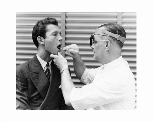 1930s 1940s doctor examining throat of a young man by Corbis