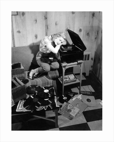 1950s teenage girl listening to music on a phonograph by Corbis