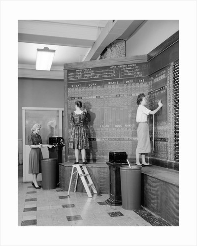 1950s 1960s women at chalkboard in brokerage house by Corbis