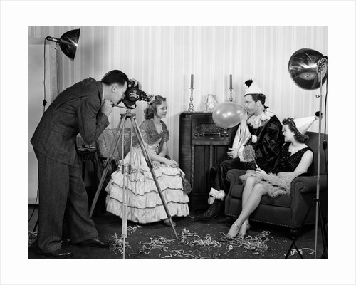 1940s photographer taking picture of young people at New Years party by Corbis