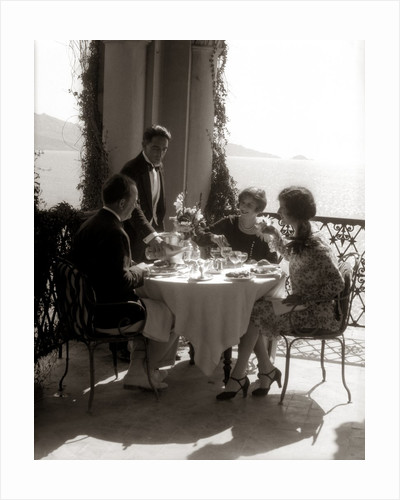 1920s group eating on balcony with waiter serving wine by Corbis