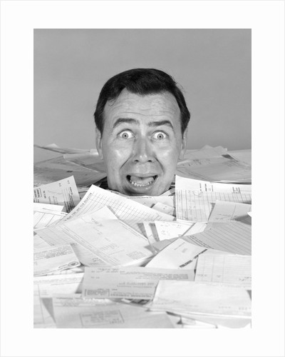 1960s portrait of bug-eyed man buried by bills by Corbis