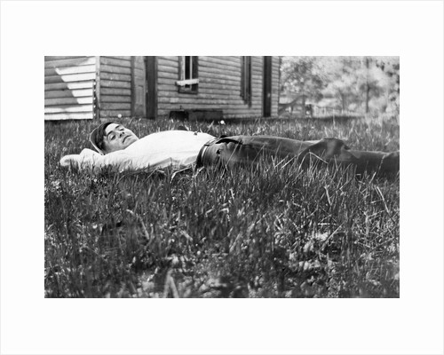 Young man lays in the grass, ca. 1912. by Corbis