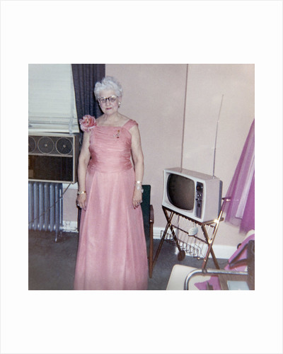 Grandma is all dressed up and standing next to a TV, ca. 1965 by Corbis