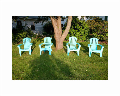 Turquois lawn chairs and green grass at sunset by Corbis