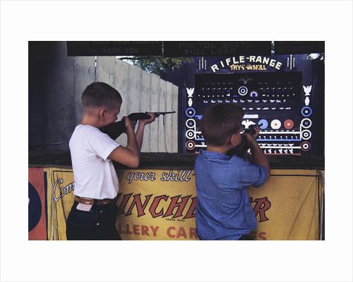 Children Firing Air Rifles at Fair Booth by Corbis