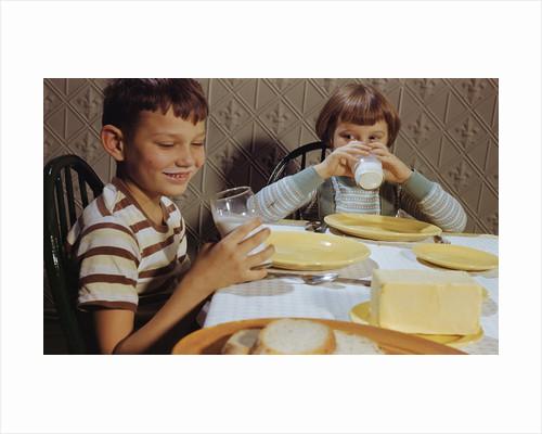 Children Drinking Milk at Dinner Table by Corbis
