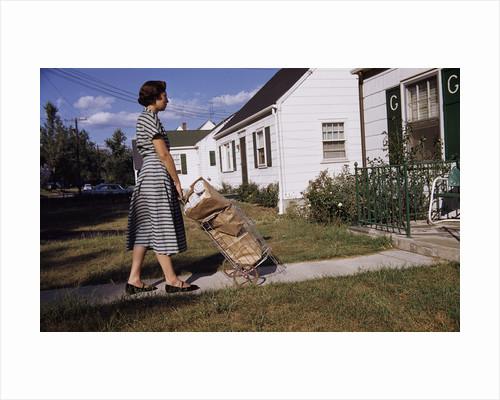 Woman Pushing Shopping Cart to House by Corbis