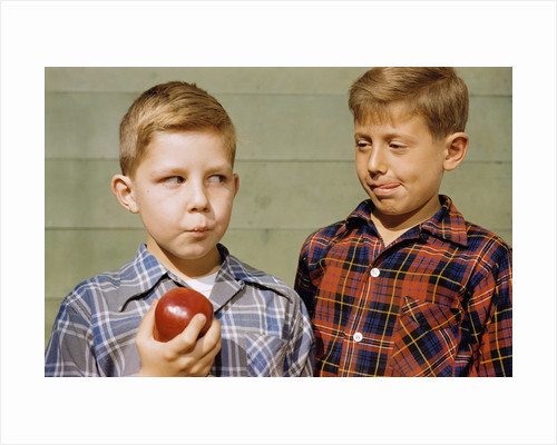 Boy Eying His Brother's Apple by Corbis