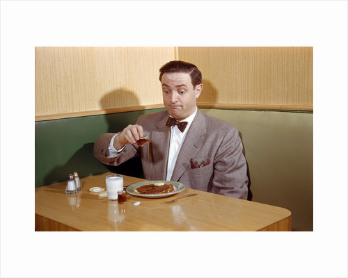 Businessman Pouring Syrup on Pancakes by Corbis