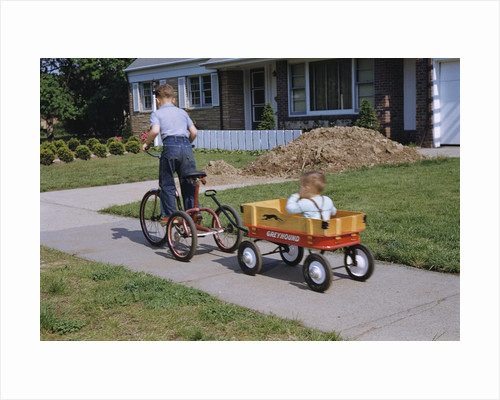 Boy Riding Tricycle and Towing Wagon by Corbis