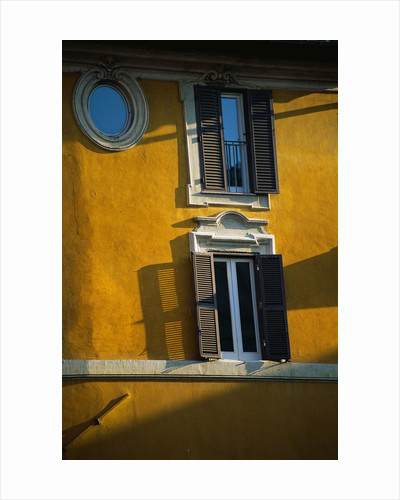 Shuttered Windows on Yellow Building by Corbis