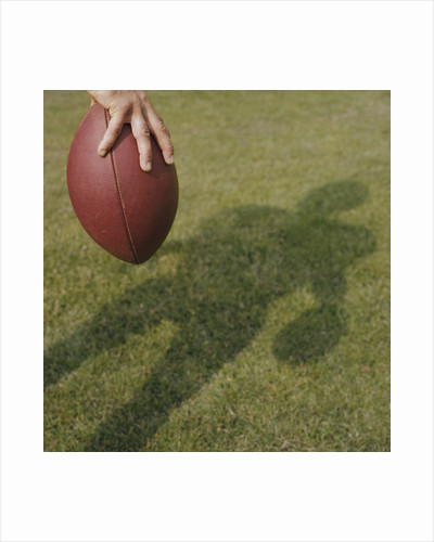 Shadow of Football Player Holding Football by Corbis