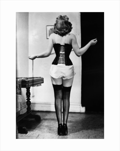 Young Woman Lacing Her Corset by Corbis