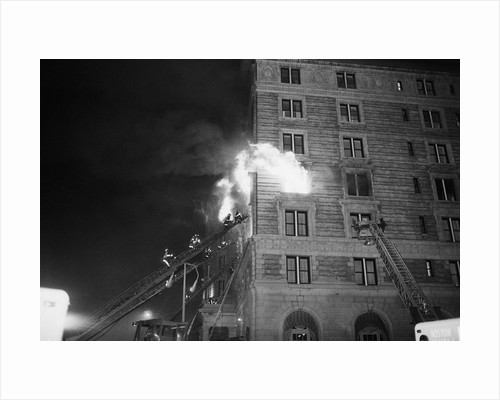 Firemen On Ladder At Flame-Engulfed Wind by Corbis