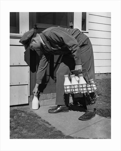 Milkman Leaving Milk Bottle on Doorstep by Corbis