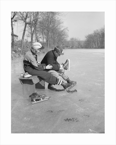Man Puts Ice Skates On Woman At Rink by Corbis