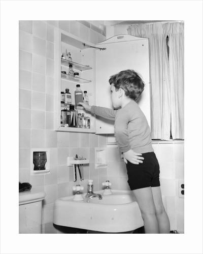 Boy Reaching into Medicine Cabinet by Corbis