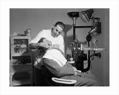 Dentist Working On Patient by Corbis