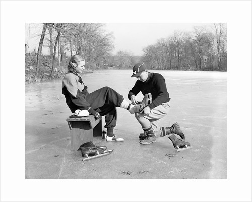 Man Putting on Woman's Ice Skates by Corbis