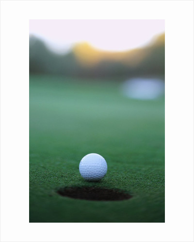 Golf Ball Close to Hole by Corbis
