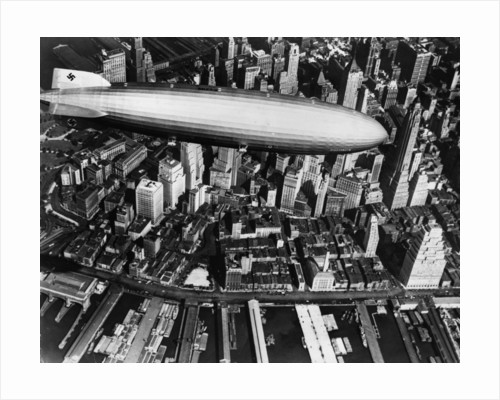 The German airship, the Hindenburg, above Manhattan, New York in 1936, on its way to its berth at Lakehurst , New Jersey, the same place where it inexplicably burst into flames the next year. by Corbis