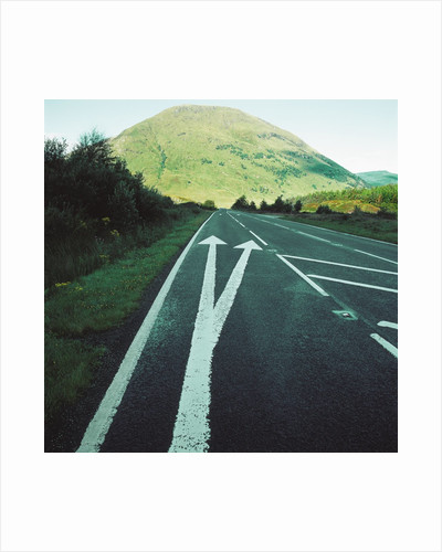 Two painted arrows on a road pointing towards a grassy mountain by Corbis