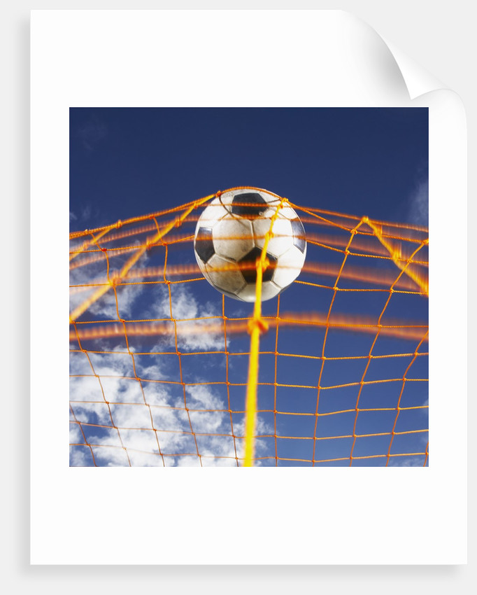 Soccer Ball Going Into Goal Net by Corbis