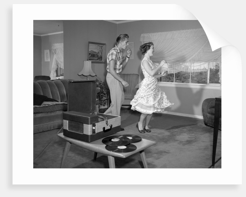1950s Laughing Teenage Couple Dancing To The Phonograph Playing 78 Rpm Records In Living Room by Corbis