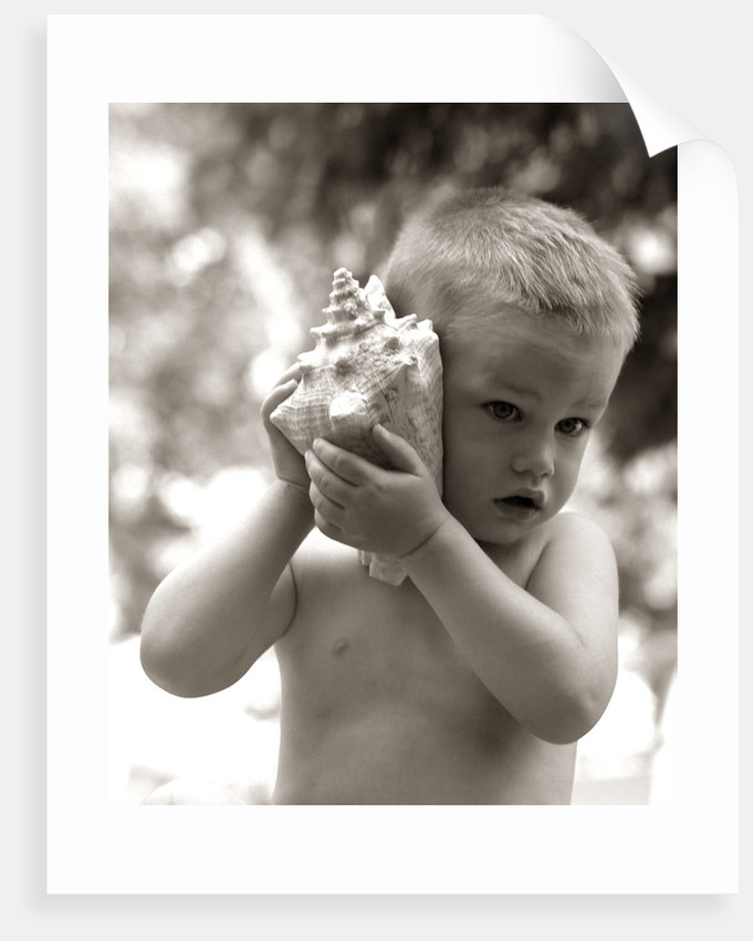 1960s Boy Toddler Holding Seashell To Ear Listening To Ocean Sounds Summer Beach by Corbis