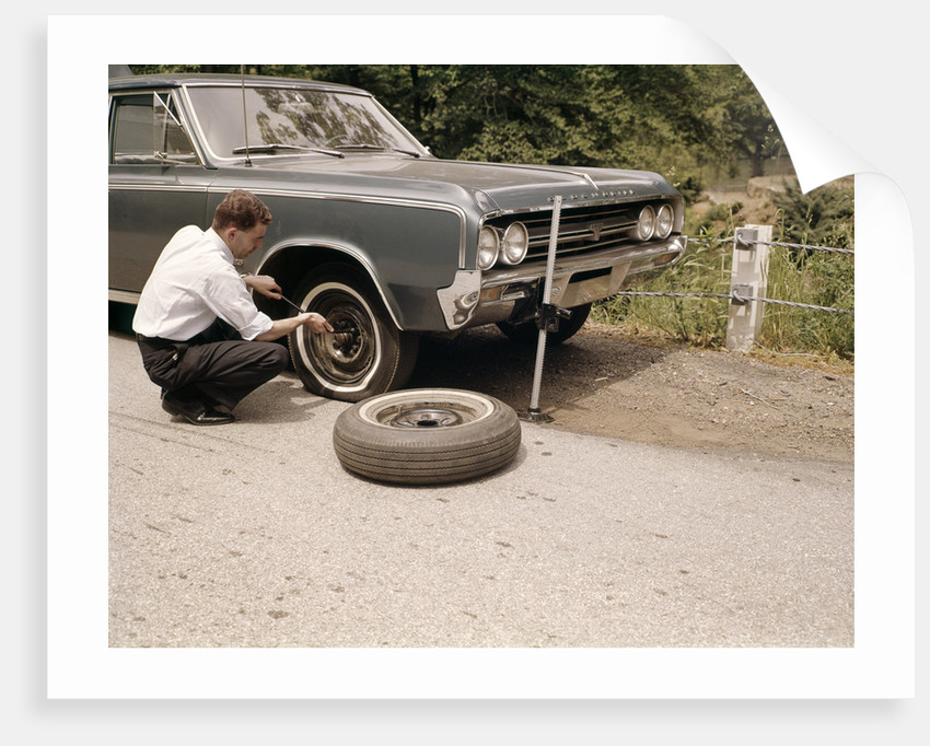 1960s Man Changing Flat Tire On Car At Side Of Rural Road Car Jack Tools Tire Iron by Corbis