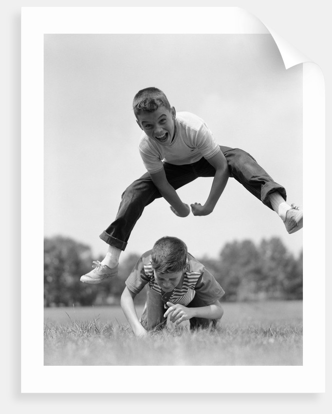 1960s Retro Boys Playing Leap Frog Outside Sky Grass Jump Jumping Crouching by Corbis