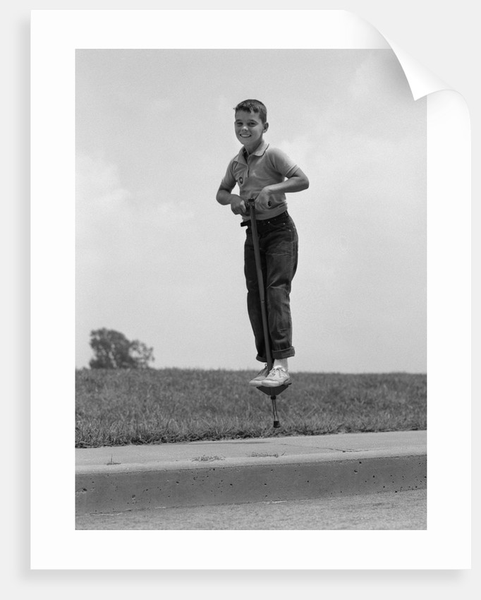 1960s boy jumping on pogo stick by corbis
