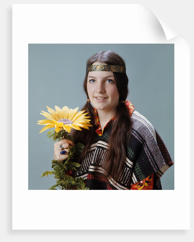 1960s 1970s Teenage Girl With Pigtails Wearing Headband And Serape Holding Sunflower by Corbis