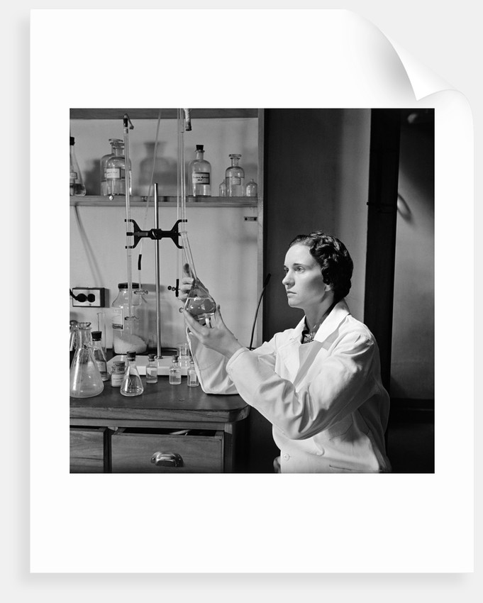 1930s 1940s Woman Scientist In Lab Coat Holding Up And Examining Beaker Of Liquid by Corbis