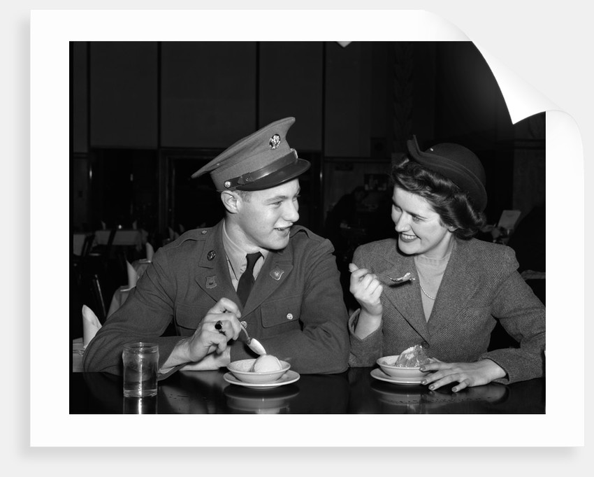1940s Soldier In Army Uniform And Girlfriend Sitting At Soda Fountain Counter Eating Dish Of Ice Cream by Corbis