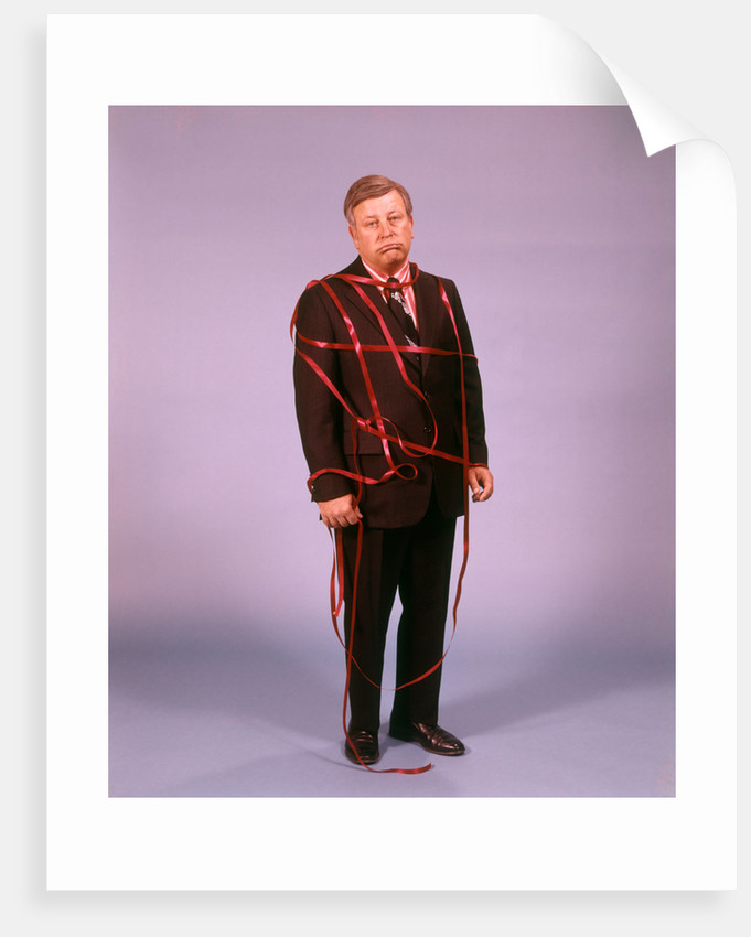 1970s Middle Aged Man Business Suit Disapointed Depressed Unhappy Tied Up In Red Tape by Corbis