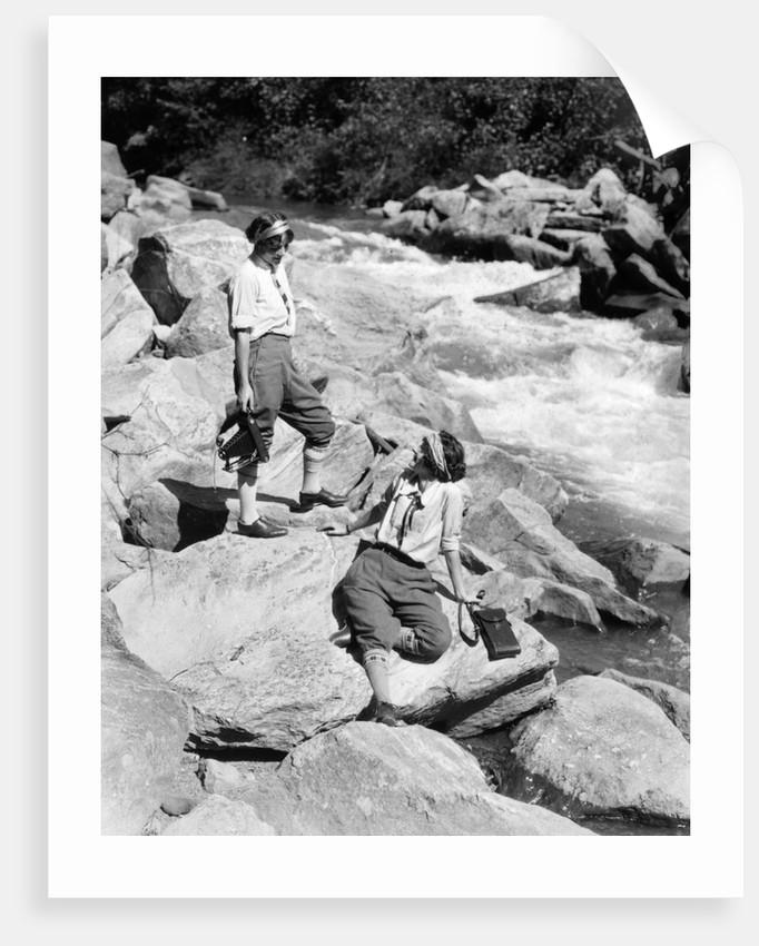 1920s Two Women Sisters On Rocks By Creek Talking Holding Folding Camera by Corbis