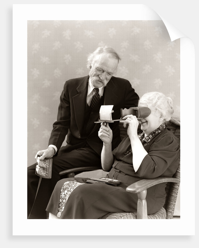 1940s Older Senior Couple Man Woman Viewing Photographs By Stereopticon Stereoscope by Corbis