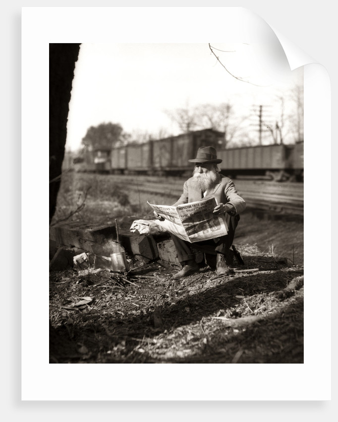 1930s Hobo Sitting By Railroad Track Reading Newspaper During Great Depression by Corbis