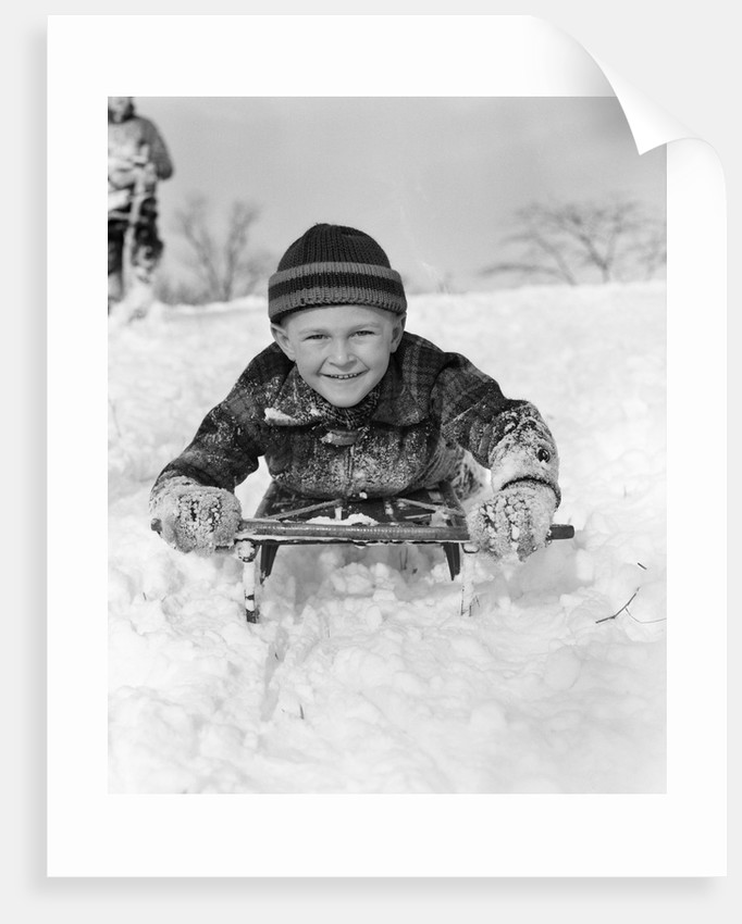 1940s Boy On Sled In Snow Facing Camera Hands And Jacket Covered In Snow by Corbis